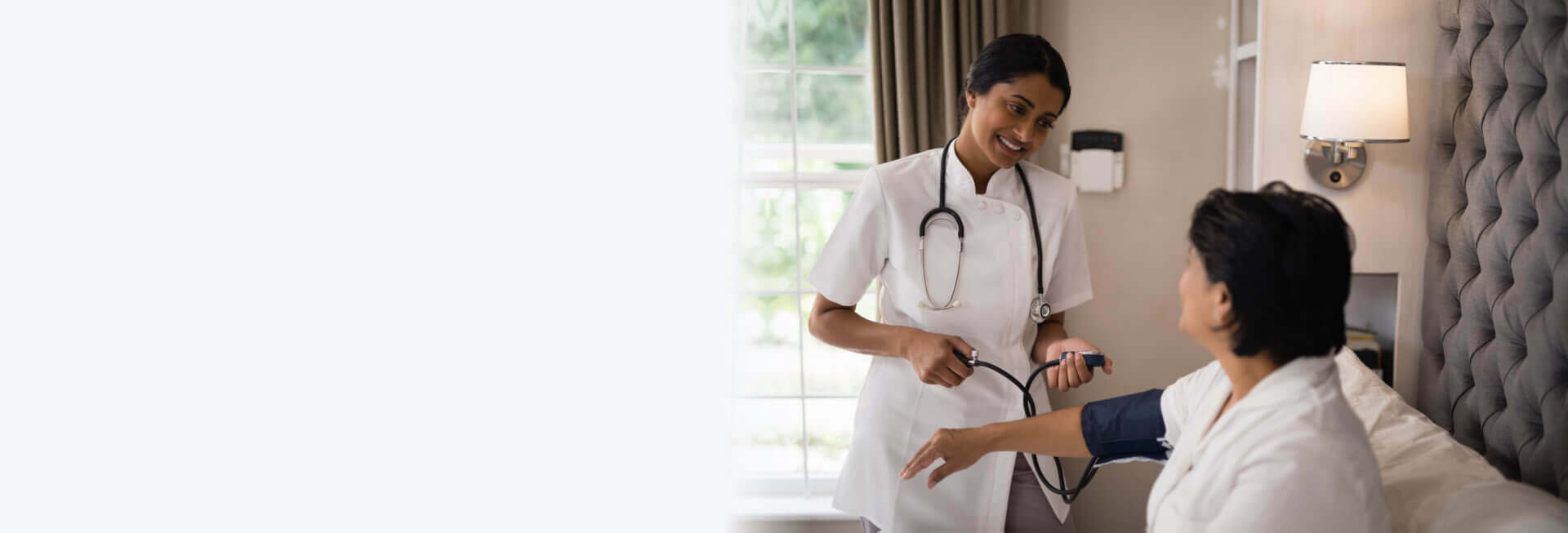 caregiver checking blood pressure of patient